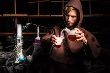 Alchemist in chemical laboratory prepares magical liquids