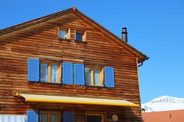 Holzhaus mit gelber Markise
