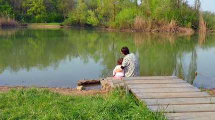 Mother Hugging Daughter And Looking At Natural Landscape