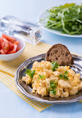 Scrambled eggs with fresh parsley on vintage metal plate
