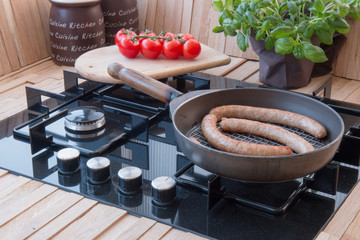 Tasty sausage in the pan on stove with vegetables