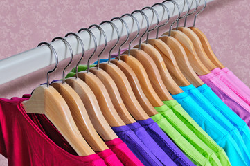 Multicolored women's t-shirts hanging on wooden hangers.