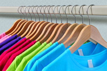 Multicolored women's t-shirts hang on wooden hangers.