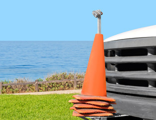 Stacked orange traffic cones mounted on truck at ocean