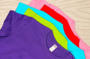 Multi-colored women's t-shirts lie on wooden background.