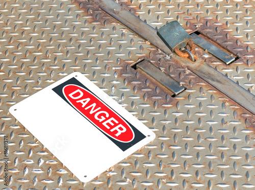 Aluminium Tunnel Locked rusty metal manhole access cover, padlock, danger sign