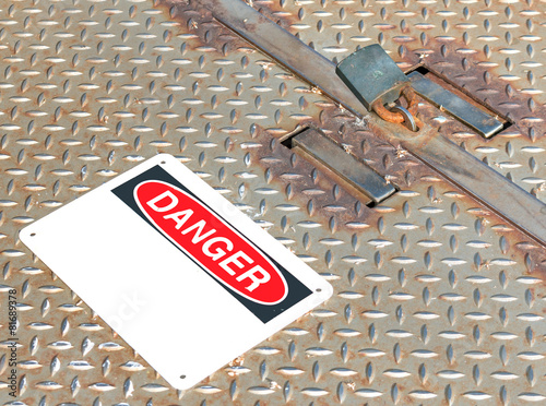 Locked rusty metal manhole access cover, padlock, danger sign - 81689378