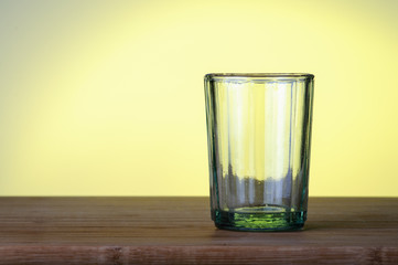 Empty glass on a yellow background