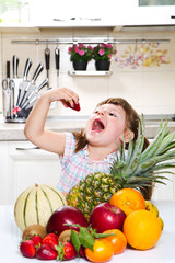 little cute girl holding and eating a strawberry in the kitchen