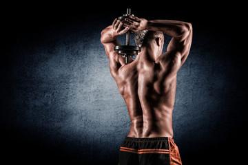 Muscular man raising behind his head dumbbells