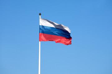Russian flag on the flagpole waving on sky
