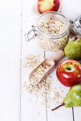 Fruits and oats over white wooden background
