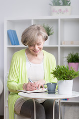 Smiling woman writing in notebook