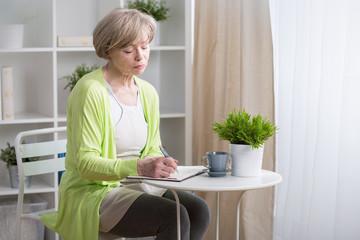 Mature woman noting in calendar
