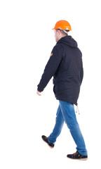 Back view of goingWorker in a helmet. walking young engineer.