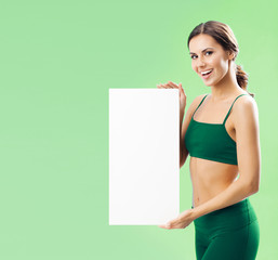 Woman in fitnesswear showing signboard, on green