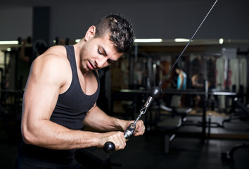Biceps and triceps young man training at gym pull
