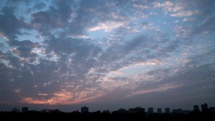 Sunset time lapse clouds over a Birmingham   silhouette skyline.
