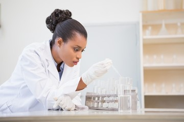 Concentrated scientist analyzing test tube