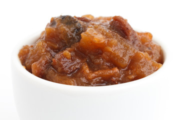 Detail of rough fruit chutney in white dish.