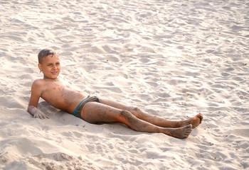 Загорелый мальчик играет на пляже