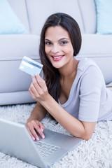 brunette lying on the floor and doing online shopping