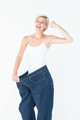 Smiling woman wearing too big jeans