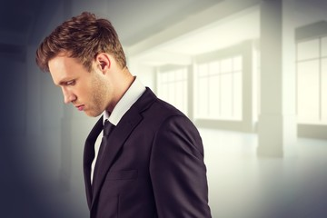 Composite image of young handsome businessman looking down