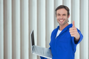 mechanic holding laptop while showing thumbs up