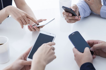 Four businessmen are using a mobile phone