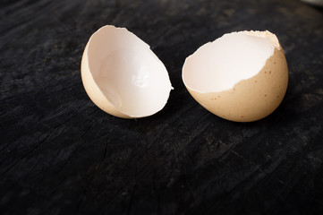 The egg shell lies on a dark kitchen table
