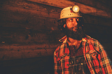 Miner Wearing Helmet Lamp Leaning Against Wall