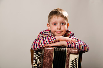 The boy crossed his arms and leaned on the accordion