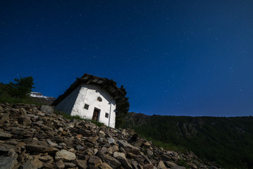 Old alpine chapel and starry sky