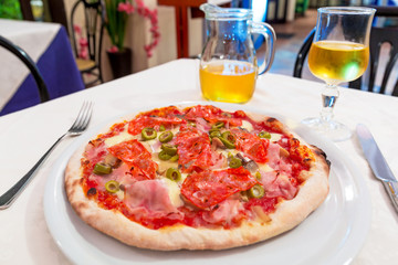 Italian pizza with ham, salami, cheese and green olives