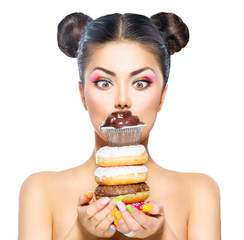 Beauty model girl taking stack of colorful donuts and muffin