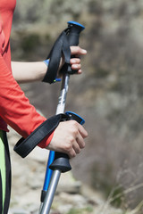 Hiker holding hiking poles with straps, close-up