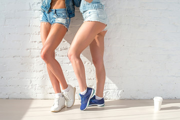 sporty long sexy legs of two beautiful women jeans shorts urban