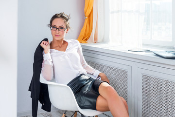 Attractive young businesswoman in glasses sitting on the chair