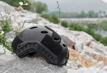 Special force Modern combat helmet on white rocks at riverside