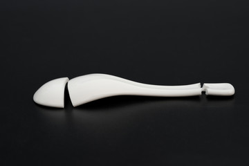 broken porcelain spoon on a black background