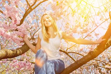Frau mit Sonne auf Ast im Kirschbaum