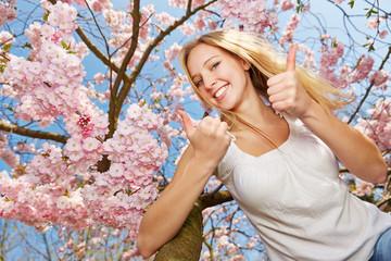 Frau hält Daumen hoch im Frühling