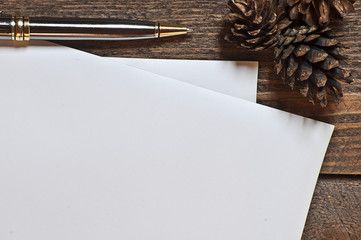 Set of pines pen and paper sheets on wooden table