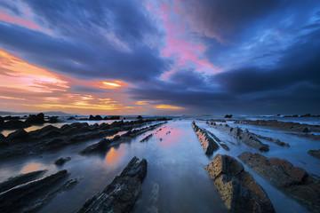 rocks in Barrika beach with dramatic sky