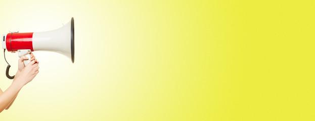 Hand hält Megafon vor Hintergrund in gelb