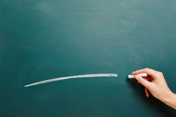Hand mit Kreide an Kreidetafel malt Linie