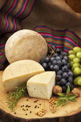 Organic cheese and grapes with walnuts and pepper on wooden log