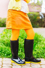 Black rain boots on child's feet, outdoors