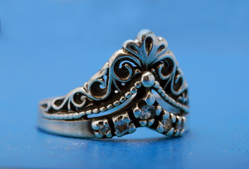 silver ring with a crown on blue